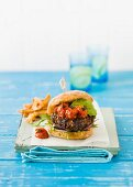 A burger with avocado and tomatoes