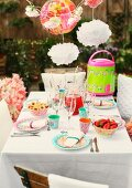 Party table set with brightly patterned plastic and paper tableware in garden