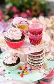 Cupcakes and colourful silicone cake cases on floral cake stand