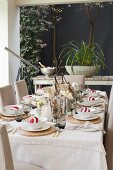 Table festively set with Christmas decorations on roofed terrace