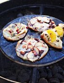 Various small pizzas on a barbecue