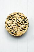 A whole blueberry pie with a lattice top in a baking tin