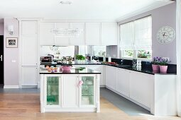 An elegant fitted kitchen with white cupboards and lilac accessories on shiny work surfaces