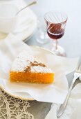 A slice of Toucinho do céu (almond and lemon cake, Portugal) with a glass of port wine