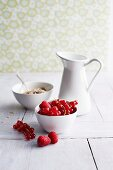 Raspberries, redcurrants, muesli and a jug of milk
