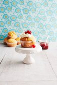A muffin topped with cream, redcurrants and redcurrant compote against a floral papered wall