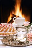 A Bundt cake and a cappuccino in front of an open fire