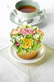 A cupcake decorated with romantic sugar flowers in front of a cup of tea