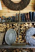 An old broom between a tray and a woven wreath on a wooden bench in front of a wood pile with a shelf of rubber boots above it