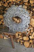 Kranz aus Geflecht auf Bank vor geschichtetem Holzlager