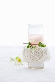 A candle in a glass with a knitted cover
