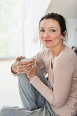 A middle-aged brunette woman with a cup of coffee