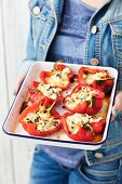 A woman holding peppers stuffed with feta and mozzarella on a baking tray