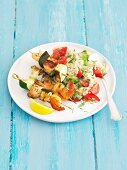 Salmon and courgette skewers with prawns served with rice and tomatoes