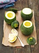 Hollowed-out, round courgettes on a piece of baking paper