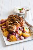 Roast lamb studded with lemons on a bed on potatoes and onions