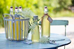 Hollerblütensirup auf Gartentisch
