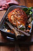 Studded pork knuckle with vegetables in a roasting tin