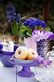 Doughnuts on a table outside decorated with crockery and blue and purple and flowers