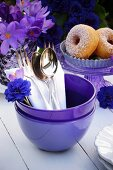 Cutlery in a purple bowl with doughnuts and purple spring flowers in the background