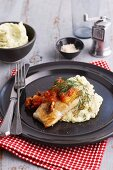 Fish fillet with tomato and olive sauce on dill mashed potatoes