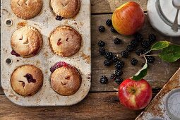 Apple and blackberry pies in a baking tin with ingredients next to it