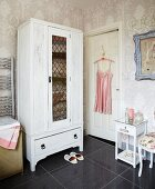 White-painted wardrobe, floral wallpaper and pink, vintage silk slip on coat hanger in bathroom