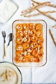 Aprikosen mit Honig und Mandelblättchen aus dem Ofen, daneben eine Honigwabe, griechischer Joghurt und Sesamgebäck