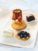 Petit fours, cannele, tartlets with lemon and mascarpone cream and blueberries, mini cheesecakes with raspberries