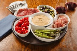 Hummus dip with ham, salami, olives and vegetables in bowls