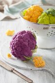 Different coloured cauliflower in a colander and on a chopping board