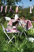 Fresh cherries and a jug of meadow flowers on a table with a checked cloth in a sunny garden