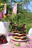 A stack of waffle with cream and fresh cherries on a plate next to a jug of wild flowers on a checked tablecloth
