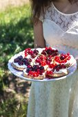 A little girl holding a plate of cherry and redcurrant tartlets