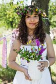 Young girl wearing white dress and wreath of flowers holding ceramic jug of wild flowers