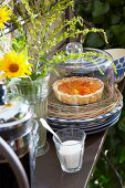 Apricot tart on a wicker plate under a glass cloche with a jug of coffee, French country house crockery and a bunch of meadow flowers on an iron shelf