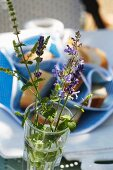 Lavender flowers and mint in a glass with an out of focus baguette basket in the background