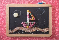 A sailing boat made from bonbons on a chalk board