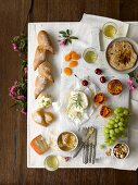 An appetiser platter featuring grilled peaches, apricots, cherries, grapes, nuts, honeycomb, bread and white wine
