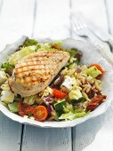 Orzo salad with fresh vegetables and grilled chicken breast