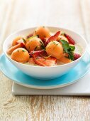 Cold melon and yogurt soup with strawberries and mint