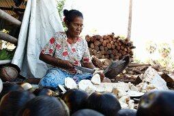A woman preparing palmyra fruits