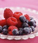 Fresh raspberries and blueberries in a glass bowl