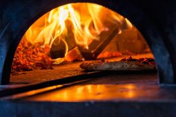 Pizza being removed from a hot oven