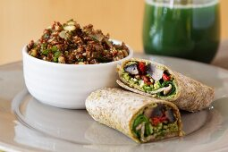 Wholemeal wraps filled with portobello mushrooms, pesto, dried tomatoes and courgettes next to a bowl of quinoa with cabbage and coconut milk