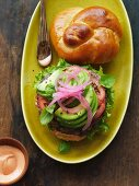 A hamburger in a brioche roll with avocado and onion on a plate