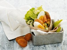 A wrap with eggs and smoked salmon in a lunch box
