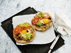 Rye bread pizzas with fried eggs, tomatoes, olives and onions
