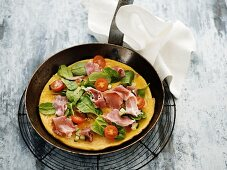 A pancake with serrano ham, spinach and cherry tomatoes