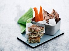 Potato and bean frittata with carrot sticks and raisin cake in a lunch box